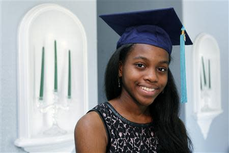 Grace Bush poses in her university graduation cap at her home in West Park, Florida, May 6, 2014. REUTERS/Andrew Innerarity