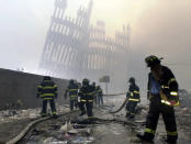 Firefighters work beneath the destroyed mullions, the vertical struts, of the World Trade Center in New York on Tuesday, Sept. 11, 2001. (AP Photo/Mark Lennihan)