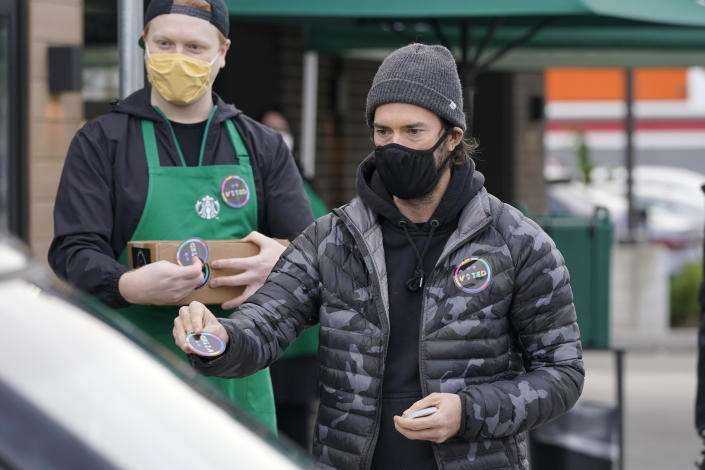 """Former Seattle Sounders MLS soccer player Brad Evans, right, hands out stickers that read """"Voted"""" to customers as he takes part in a get-out-the-vote event at a Starbucks store, Tuesday, Oct. 27, 2020, in Seattle's White Center neighborhood. Washington is a vote by mail state, and thousands of ballots have already been mailed back, dropped off in boxes, or cast in person. (AP Photo/Ted S. Warren)"""