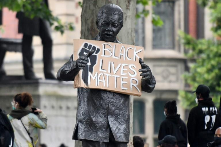 A statue of Nelson Mandela is seen holding a Black Lives Matter placard in London's Parliament Square as demonstrators show solidarity with the Black Lives Matter movement in the wake of the George Floyd killing (AFP Photo/JUSTIN TALLIS)