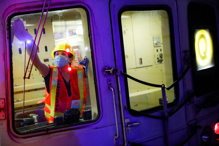 A contractor cleans a subway car at the 96th Street station to control the spread of COVID-19, Thursday, July 2, 2020, in New York.