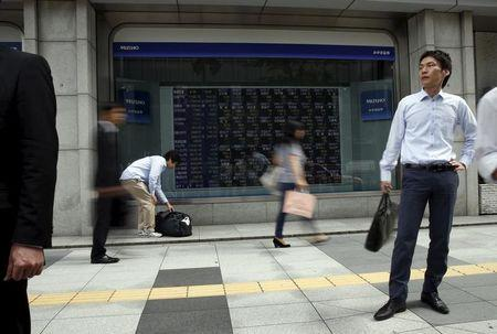 FILE PHOTO: Passersby walk past in front of stock quotation board outside a brokerage in Tokyo, Japan, September 29, 2015. REUTERS/Issei Kato