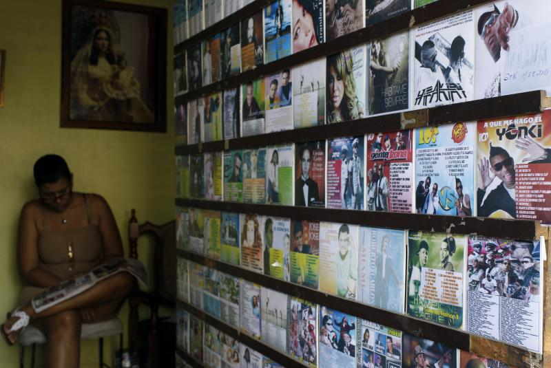 """In this Jan. 4, 2013 photo, a woman selling reggeaton music, right, and movies sits at the store run out of a home in Havana, Cuba. Cuban authorities have recently announced restrictions reportedly declaring state-run recording studios and broadcasts off-limits to songs with questionable lyrics. They also prohibit such music in performance spaces subject to government control. The rules would theoretically apply to all genres, but it's reggaeton that leading cultural lights have singled out for criticism in official media while warning of new rules governing """"public uses of music."""" (AP Photo/Franklin Reyes)"""