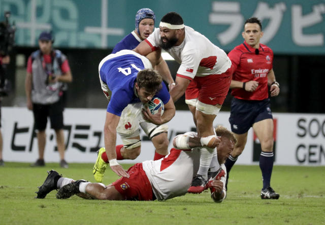France's Damian Penaud is tackled by Tongan defenders during the Rugby World Cup Pool C game at Kumamoto Stadium between France and Tonga in Kumamoto, Japan, Sunday, Oct. 6, 2019. (AP Photo/Aaron Favila)