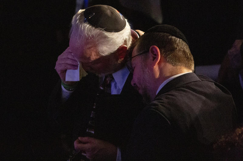 Rabbi Jeffrey Myers, center, of the Tree of Life/Or L'Simcha Congregation, is comforted after saying a prayer for the souls of the deceased during the one-year commemoration of the Tree of Life synagogue attack, at Soldiers & Sailors Memorial Hall and Museum, Sunday, Oct. 27, 2019, in Pittsburgh. (AP Photo/Rebecca Droke)
