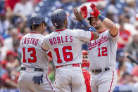 Washington Nationals' Kyle Schwarber (12) is congratulated by Starlin Castro (13) and Victor Robles (16) after hitting a three-run homer during the fifth inning of a baseball game against the Philadelphia Phillies, Wednesday, June 23, 2021, in Philadelphia. (AP Photo/Laurence Kesterson)