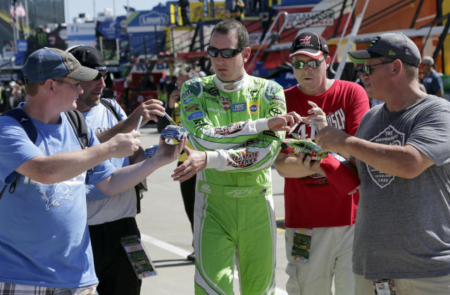 FILE - In this Sunday Oct. 6, 2017, file photo, Kyle Busch signs autographs for fans before practice for a NASCAR Cup Series auto race at Charlotte Motor Speedway in Concord, N.C. Some fans have been coming to the Coca-Cola 600 for decades, but they won't be allowed into Charlotte Motor Speedwaý on Sunday due to Covid-19, leaving the grandstands empty and many disappointed. (AP Photo/Chuck Burton, File)