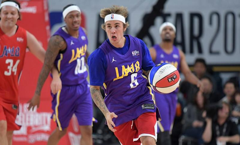 Recording artist Justin Bieber dribbles the ball during the NBA All-Star Celebrity Game at the Los Angeles Convention Center. Reuters