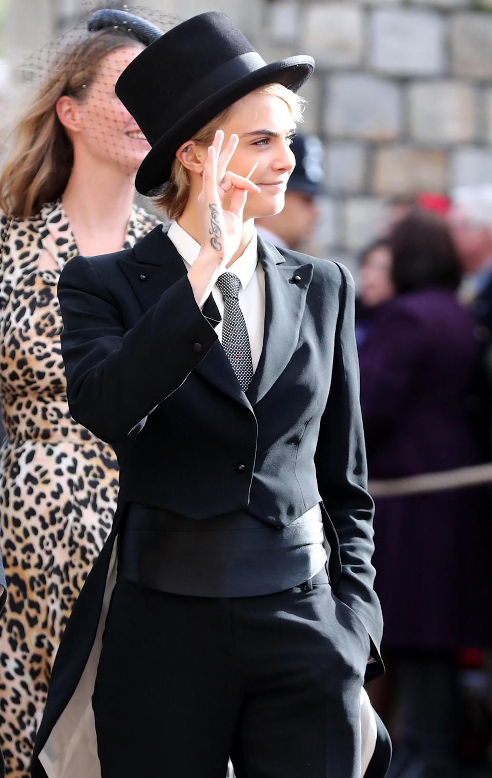 Cara Delevingne turned heads in a top hat and suit. (Photo: Getty Images)