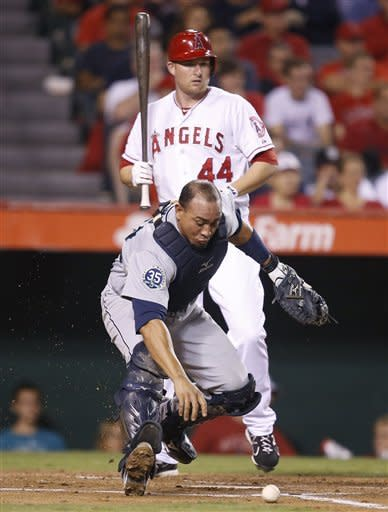 Seattle Mariners catcher Miguel Olivo tries to grab the ball as Los Angeles Angels' Mark Trumbo, background, watches during the second inning of a baseball game in Anaheim, Calif., Wednesday, Sept. 26, 2012. (AP Photo/Jae C. Hong)