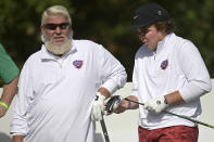 John Daly, left, watches as his son Little John Daly prepares to tee off on the first hole during the first round of the PNC Championship golf tournament, Saturday, Dec. 19, 2020, in Orlando, Fla. (AP Photo/Phelan M. Ebenhack)