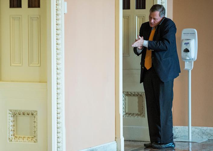 Sen. Richard Burr (R-N.C.) sanitizes his hands while talking on his cell phone outside the Mansfield Room in the Capitol on Jan. 8, 2015.