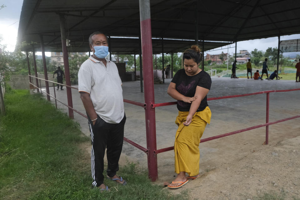 Diana Khumanthem, 30, stands beside her father Yaima Khumanthem, 75, in a public gathering space where Yaima chooses to spend his day after his wife and daughter died of COVID-19, in Imphal, in Manipur, India, Monday, June 28, 2021. Life is tentatively returning to normal in India as coronavirus cases fall. But millions are embroiled in a nightmare of huge piles of medical bills. Most Indians don't have health insurance and costs for COVID-19 treatment have them drowning in debt. (AP Photo/Yirmiyan Arthur)