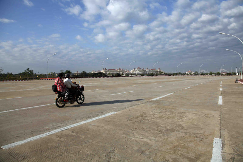 In this Tuesday, Nov. 26, 2013 photo, two men on a motorbike head toward the Parliament complex, seen center, along one of the many multi-lane but virtually empty highways in Myanmar's surreal, eight-year-old capital of Naypyitaw. Controversy continues whether the remote, built-from-scratch city will become a viable place or a white elephant. But the green, clean, traffic-free capital has gathered some momentum and will host the Southeast Asian Games this month. (AP Photo/Khin Maung Win)