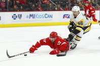 Detroit Red Wings defenseman Filip Hronek (17) tries to control the puck from Pittsburgh Penguins center Zach Aston-Reese (46) in the third period of an NHL hockey game Saturday, Dec. 7, 2019, in Detroit. (AP Photo/Paul Sancya)
