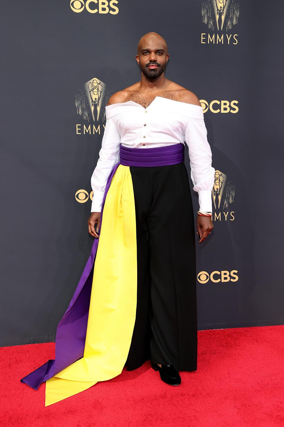 The <em>Hacks</em> actor added a purple and gold sash to his off-the-shoulder look for an extra pop.
