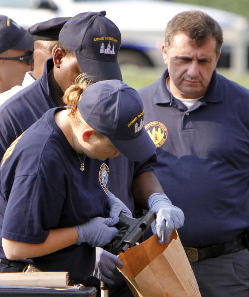 Crime scene investigators look over an officer's handgun after the off-duty Philadelphia police officer was shot and mortally wounded, Saturday, Aug. 18, 2012, in North Philadelphia. Police said the officer had just gotten off his overnight shift and was not wearing his uniform as he walked along Cecil B. Moore Avenue, where he was shot multiple times just before 6 a.m., Saturday. The officer later died at the hospital. (AP Photo/ Joseph Kaczmarek)