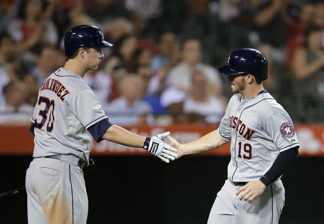 Houston Astros' Robbie Grossman, right, is greeted by Matt Dominguez after scoring on a sacrifice fly by Chris Carter during the fifth inning of a baseball game against the Los Angeles Angels on Friday, Aug. 16, 2013, in Anaheim, Calif. (AP Photo/Jae C. Hong)