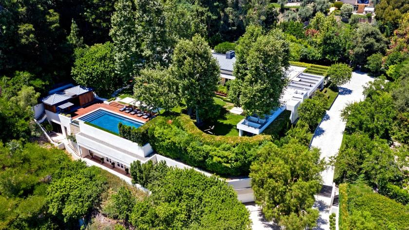 The three-acre compound includes a 9,000-square-foot main house, two guesthouses, a pool house, detached gym and underground garage.