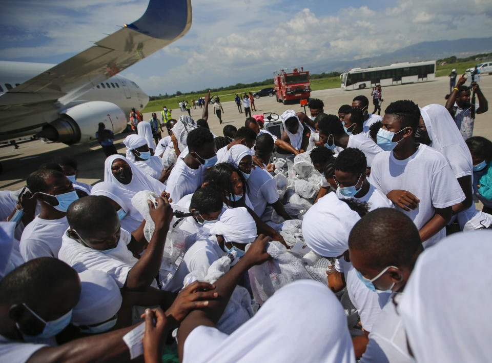 Haitians deported from the United States recover their belongings on the tarmac of the Toussaint Louverture airport in Port-au-Prince, Haiti Tuesday, Sept. 21, 2021 (AP Photo/Joseph Odelyn)