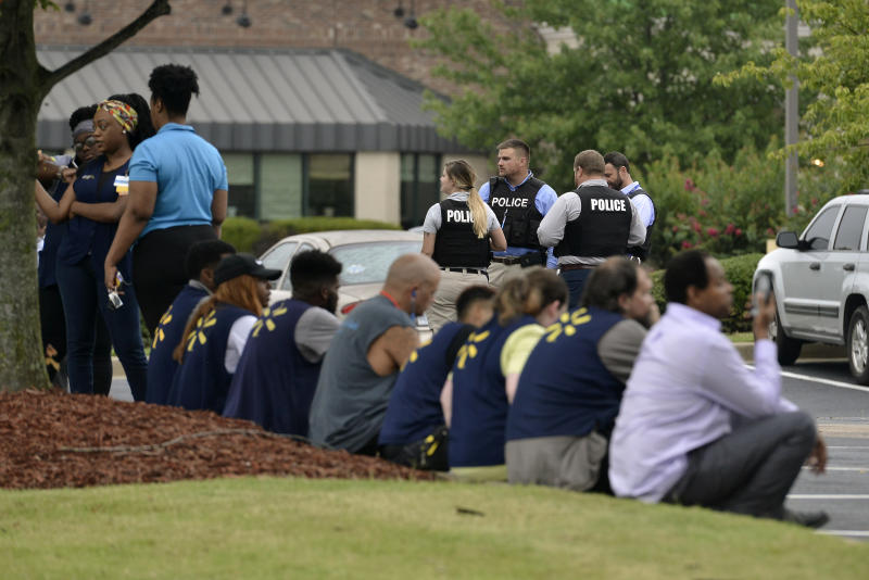 Officers and employees gather in a nearby parking lot after a shooting at a Walmart store Tuesday, July 30, 2019 in Southaven, Miss. (AP Photo/Brandon Dill)