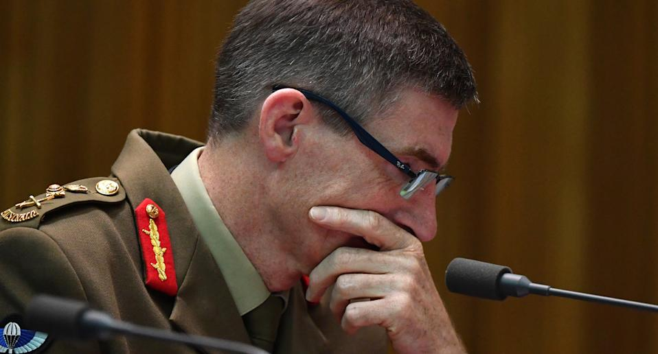 General Angus Campbell holds face in hands while seated at microphone.