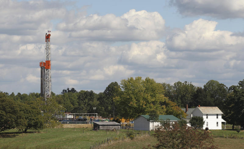 This Wednesday, Sept. 19, 2012 photo, shows a drill rig across the street from a farmhouse in Carrollton, Ohio. Rural Carroll County boasts more active oil and gas wells than any other county in Ohio, and the tax dollars are flowing right along with the crude. (AP Photo/Tony Dejak)