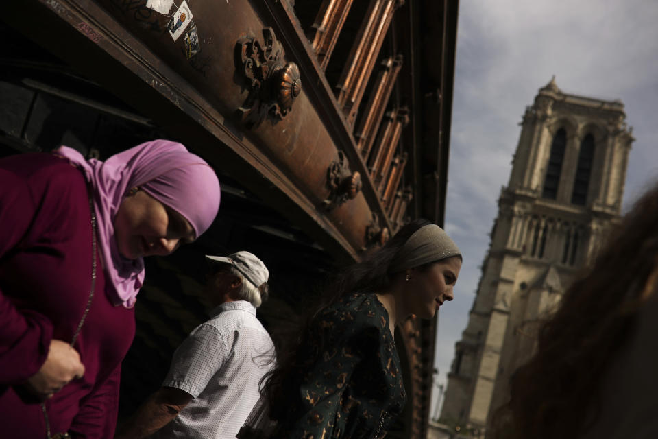 People walk past the Notre Dame cathedral in Paris, Monday, April 22, 2019. In the wake of the fire last week that gutted Notre Dame, questions are being raised about the state of thousands of other cathedrals, palaces and village spires that have turned France — as well as Italy, Britain and Spain — into open air museums of Western civilization. (AP Photo/Francisco Seco)