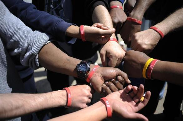 Job seekers show their wristbands, signifying which spot they are in line, as they wait in front of the training offices of Local Union 46, the union representing metallic lathers and reinforcing ironworkers, in the Queens borough of New York, April 29, 2012.