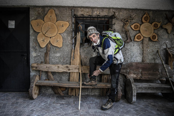 """In this image taken on Thursday, April 23, 2020, alpine guide Ernesto Cocchetti, 57, puts on his hiking boots as he prepares to go walking, in Castione Della Presolana, near Bergamo, northern Italy. Cocchetti predicts a return to """"living with nature's rhythms"""" once government restrictions to prevent the spread of COVID-19 will be eased. (AP Photo/Luca Bruno)"""