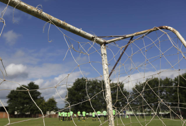 In this May 28, 2014 photo, a worn out net and goal post stand at the end of the field where the Presidente Prudente soccer club's under 16 category trains in Presidente Prudente, Brazil. Professional soccer in the World Cup host nation is struggling, with lower-division teams unable to play enough games, players forced to take multiple jobs and even top-tier teams competing in mostly empty stadiums. (AP Photo/Andre Penner)
