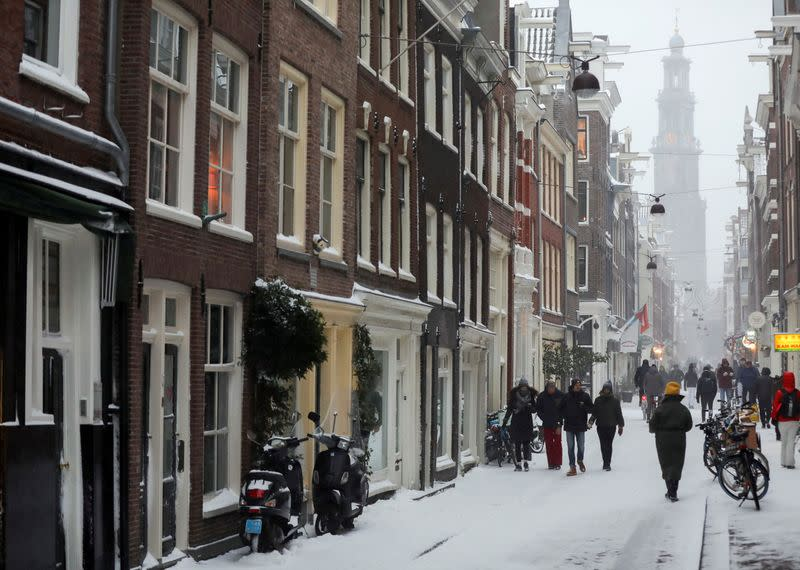 FILE PHOTO: People walk after heavy snowfall in Amsterdam