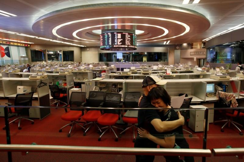 Catherine Cheung is hugged by her colleague before leaving the trading hall of the Hong Kong Exchanges in Hong Kong