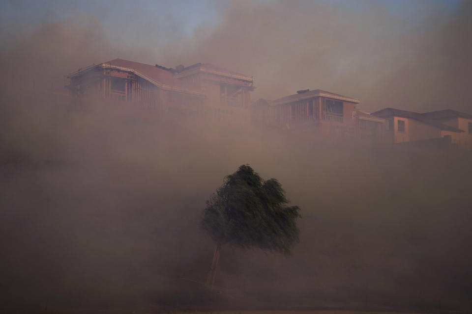 Gusting winds carry smoke from the Silverado Fire into residential areas Monday, Oct. 26, 2020, in Irvine, Calif. A fast-moving wildfire forced evacuation orders for 60,000 people in Southern California on Monday as powerful winds across the state prompted power to be cut to hundreds of thousands to prevent utility equipment from sparking new blazes. (AP Photo/Jae C. Hong)