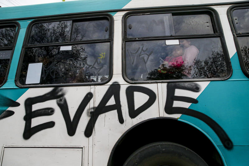 """People travel in a bus painted with graffiti that reads in Spanish """"Evade,"""" in Santiago, Chile, Saturday, Oct. 19, 2019. Chile has been facing protests that started on Friday afternoon when high school students flooded subway stations, jumping turnstiles, dodging fares and vandalizing stations as part of protests against a fare hike, but by nightfall had extended throughout Santiago with students setting up barricades and fires at the entrances to subway stations, forcing President Sebastian Pinera to announce a state of emergency and deploy the armed forces into the streets. (AP Photo/Esteban Felix)"""