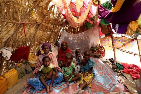 A family is pictured in their straw grass home at the IDP camp at Gamboru, Borno