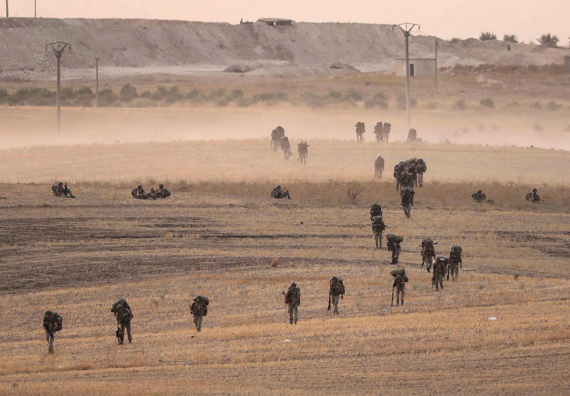 In this Monday, Oct.14, 2019 photo made available Tuesday, Oct. 15, 2019, Turkey's forces advance towards Manbij, Syria. U.S. military spokesman says U.S. forces have left Kurdish-held town of Manbij, part of withdrawal from northeast Syria. (Ugur Can/DHA via AP)