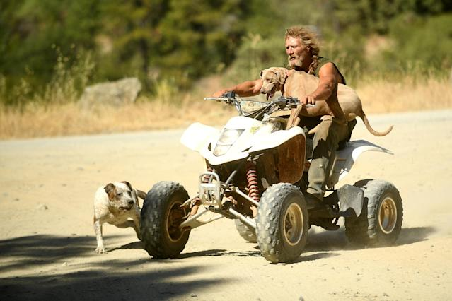 <p>Ponderosa fire evacuee Lynn, who declined to give a last name, rides with his dog Bugs Buggy while watching the fire burn east of Oroville, Calif., Aug. 30, 2017. (Photo: Noah Berger/Reuters) </p>