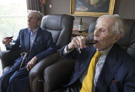 The world's oldest living twin brothers, Paulus (L) and Pieter Langerock from Belgium, 102, drink wine while sitting in their living room at the Ter Venne care home in Sint-Martens-Latem, Belgium, August 11, 2015. REUTERS/Yves Herman