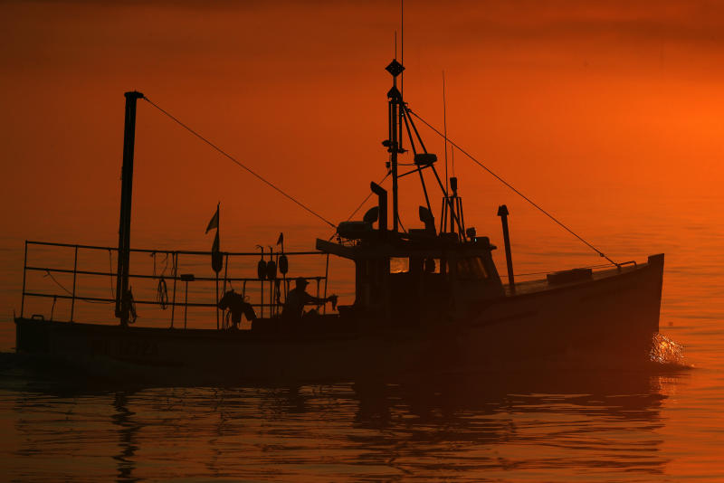 FILE - In this July 2019 file photo, a lobster boat heads out to sea at dawn off South Portland, Maine. It's a slow lobster season so far in Maine, but fishermen are still hopeful it'll be a good one. The harvest of crustaceans in America's biggest lobstering state is usually in full swing by July, but fishermen say they aren't catching much.  (AP Photo/Robert F. Bukaty, File)