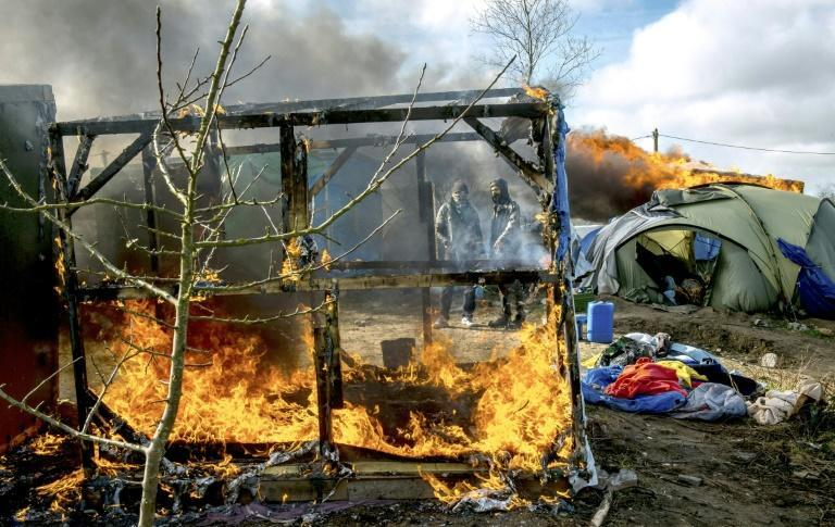 """Shelters burn in the """"Jungle"""" migrant camp in the French port city of Calais on March 3, 2016"""