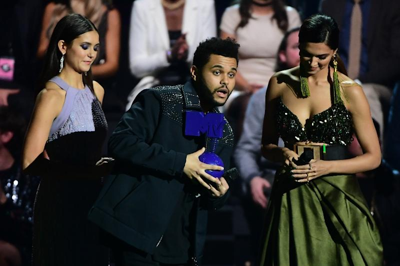 Canadian singer The Weeknd (C) receives the Best Video Award from Bulgarian-Canadian actress Nina Dobrev (L) and Indian film actress Deepika Padukone at the MTV Europe Music Awards on November 6, 2016 (AFP Photo/Emmanuel Dunand)