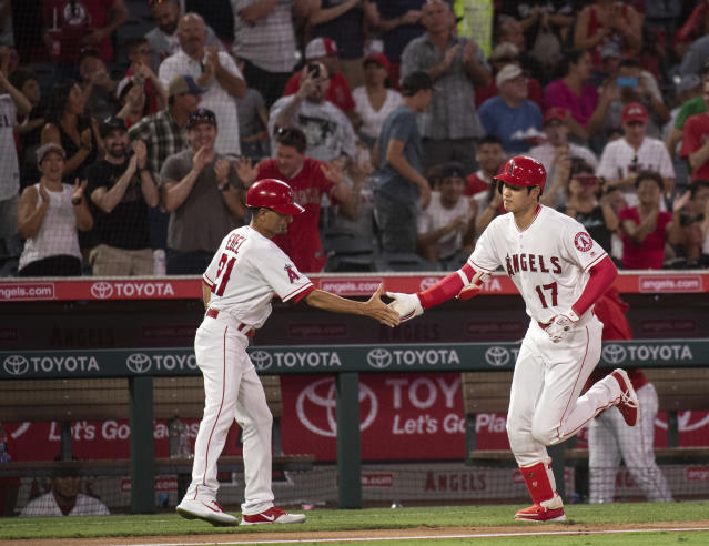 Los Angeles Angels' Shohei Ohtani, right, celebrates his solo home run with third base coach Dino Ebel during the fourth inning of a baseball game against the Chicago White Sox in Anaheim, Calif., Monday, July 23, 2018. (AP Photo/Kyusung Gong)
