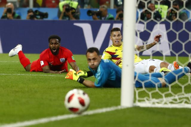 <p>Danny Rose, Mateus Uribe, and goalkeeper David Ospina all watch as the Englishman's shot rolls just wide of the post </p>
