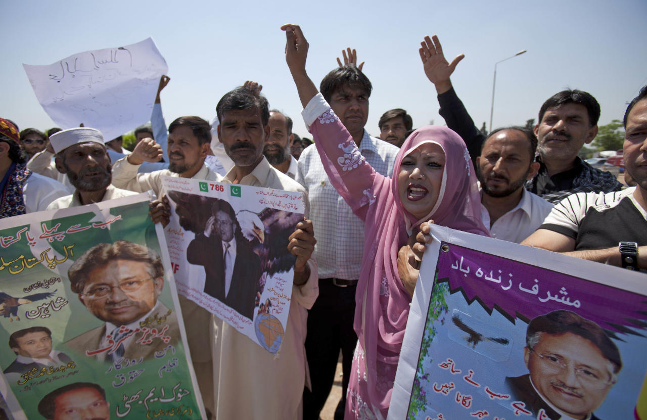 """Supporters of Pakistan's former President and military ruler Pervez Musharraf chant slogans against the court decision outside Musharraf's house in Islamabad, Pakistan on Thursday, April 18, 2013. Musharraf and his security team pushed past policemen and sped away from a court in the country's capital on Thursday after his bail was revoked in a case in which he is accused of treason. Placards read """"long live Musharraf."""" (AP Photo/B.K. Bangash)"""
