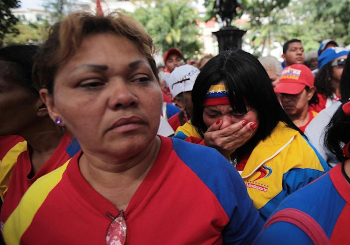 """A woman, right, reacts during a demonstration in support of Venezuela's President Hugo Chavez at the Simon Bolivar square in Caracas, Venezuela, Sunday Dec. 9, 2012. Chavez was heading back to Cuba on Sunday for more cancer surgery after announcing that the illness returned despite two previous operations, chemotherapy and radiation treatment. Chavez said Saturday that if there are """"circumstances that prevent me from exercising the presidency further"""" Vice-President Nicolas Maduro should replace him for the remainder of his term.(AP Photo/Fernando Llano)"""