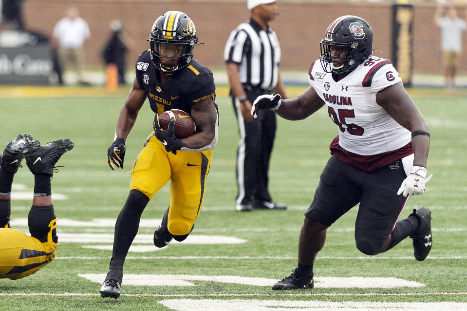 Missouri running back Tyler Badie, left, runs past South Carolina defensive lineman Kobe Smith, right, during the third quarter of an NCAA college football game, Saturday, Sept. 21, 2019, in Columbia, Mo. (AP Photo/L.G. Patterson)