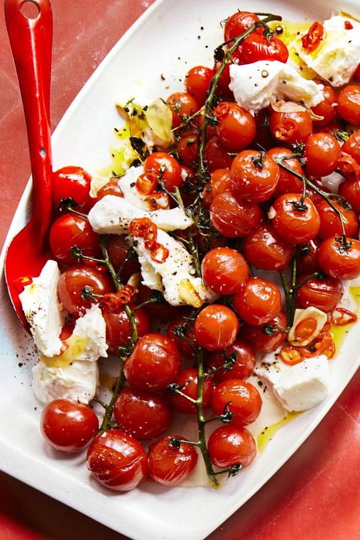"""<p>This refreshing salad comes together with just a handful of ingredients. </p><p><a href=""""https://www.womansday.com/food-recipes/food-drinks/a22071226/chile-roasted-cherry-tomatoes-and-fresh-mozzarella-recipe/"""" rel=""""nofollow noopener"""" target=""""_blank"""" data-ylk=""""slk:Get the recipe for Chile-Roasted Cherry Tomatoes and Fresh Mozzarella."""" class=""""link rapid-noclick-resp""""><u><em>Get the recipe for Chile-Roasted Cherry Tomatoes and Fresh Mozzarella. </em></u></a></p>"""