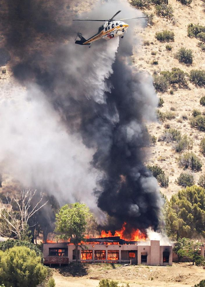A helicopter hovers amid a black plume of smoke as a house below is fully engulfed in flames.