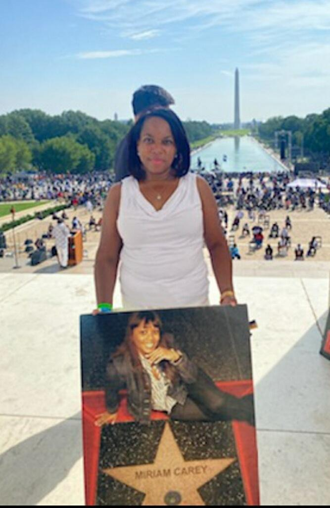 Valarie Carey Reaves-Bey holds a picture of her sister Miriam Carey during the March on Washington at the Lincoln Memorial, Aug. 28, 2020.